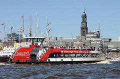 Die Hafenfähre HARMONIE mit vielen Passagieren auf dem Oberdeck fährt zum Anleger Sandtorhöft - im Hintergrund das Verwaltungsgebäude von Gruner + Jahr am Baumwall und der Turm der St. Michaeliskirche.