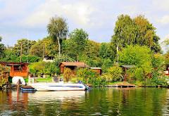 Schrebergarten auf der Billeinsel - kleine Holzlauben stehen auf den Parzellen, die alle einen Bootsanleger am Bullenhusener Kanal haben - ein Motorboot liegt im Wasser.