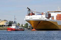 Schlepper mit RoRo-Frachtschiff vor Hamburg Steinwerder - Zelt des Musicals König der Löwen im Hamburger Hafen.