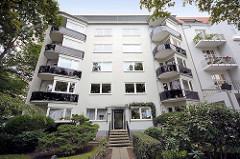 Architekturfotos aus Hamburg Winterhude, Sierichstrasse - Wohnhaus der 1950er Jahre, weisse Fassade - schwarze Balkonverkleidung.