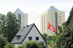 Einzelhaus mit Spitzdach und Hamburg Fahne im Vorgarten - im Hintergrund Hochhäuser von Hamburg Lohbrügge Nord - auf dem Dach befinden sich Fotovoltaikanlagen zur Energiegewinnung.