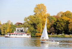 Herbstbäume am Ufer des Alstersees beim ehem. Uhlenhorster Fährhaus - Alsterdampfer und Segelboot in Fahrt.