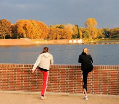Zwei Joggerinnen machen Lockerungsübungen an der Kaskade vom Stadtparksee im Stadtpark von Hamburg Winterhude - am gegenüber liegenden Seeufer hohe Bäume in Herbstfärbung.