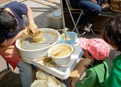 Biohof Gut Wulksfelde - Bauernmarkt. Aussteller präsentieren ihre Bioprodukte und Kunsthandwerk. Eine Töpferin dreht einen kleinen Krug - Kinder sehen ihr dabei zu.