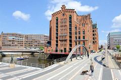 Fotos aus dem Hamburger Stadtteil Hafencity - rechts die Busanbrücke und das historische Speichergebäude des Maritimen Museums; lks. kommt eine Ausflugsbarkasse aus den Kanälen der Speicherstadt - am Ufer steht das Störtebeker Denkmal.