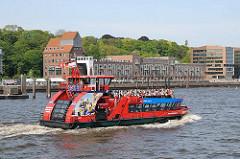 Vollbesetzte Hafenfähre auf der Elbe vor Hamburg Ottensen. Am Ufer der alte Altonaer Kaispeicher, der zur Büro- und Gastronomienutzung umgebaut wurde.