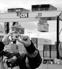 Arbeiterfotografie; Hafenarbeiter mit Kamera, Fotoapparat auf dem Container Terminal Altenwerder - im Hintergrund werden Container transportiert.