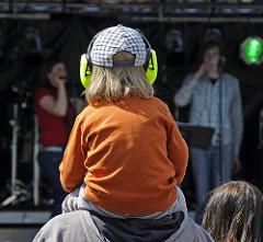 Musikveranstaltung auf dem Osterstrassenfest - verschiedene Band treten auf dem Strassenfest auf - Ein Kind sitzt auf den Schultern seinses Vaters und hat gegen den Lärm der Musik Ohrschützer auf.