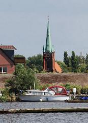 Sportboothafen am Moorfleeter Deich. Kirchturm der St. Nilolaikirche hinter dem Elbdeich.