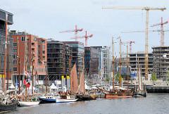 Moderne Hamburger Architektur am Sandtorkai - an den Pontons des Traditionsschiffhafens Segelboote. Im Hintergrund die Baukräne an der BAustelle des Überseequartiers.