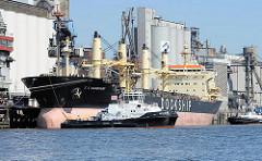 Die Ladung des Massengutfrachters C S VANGUARD ist gelöscht, das Schiff legt im Hamburger Hafen an der Süderelbe / Wilhelmsburger Neuhöfer Kanal ab.  Zwei Hafenschlepper bereiten sich darauf vor, das Frachtschiff in die Süderelbe zu schleppen.