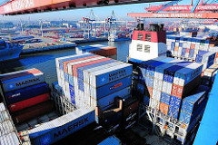 Deck des Containerfrachters CMA CGM Christophe Colomb - die Metallboxen sind hoch gestapelt, in der Bildmitte der Schornstein des Schiffs - auf den anderen Seite des Waltershofer Hafens das Containerterminal EUROGATE.