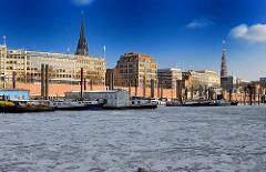 Blick in den Hamburger Binnenhafen im Winter - eisbedecktes Hafenwasser, Kontorhäuser an den Kajen, Kirchtürme, Blauer Himmel.