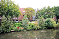 Blick über den Goldbekkanal zu den Schrebergärten am Kanalufer - dahinter die Backsteingebäude der Winterhuder Jarrestadt.