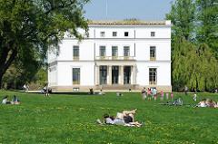 Sonntagnachmittag in der Frühlingssonne auf der Liegewiese vor dem historischen Jenischhaus in Hamburg Othmarschen.