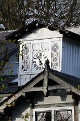 Holzgiebel und Dachfirst aus Holz - historische Archtitektur - Schnitzerei und Uhr am Dacherker - Ansorgestrasse in Hamburg Othmarschen