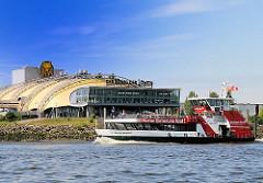 Hadag Hafenfähre auf der Elbe vor Hamburg Steinwerder - Zelt des Musicals König der Löwen am Elbufer.