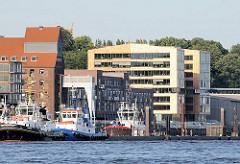 Elbufer mit Liegeplatzen von Hafenschleppern vor Neumühlen - Das rechte Gebäude gehört noch zum Stadtteil Altona Altstadt während lks. der Altonaer Kaispeicher zu Hamburg Othmarschen gehört.