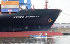 Bug des Containerfrachters KYOTO EXPRESS - am Kai des Containerterminals Altenwerder - ein schnelle Motorboot der Hamburger Wasserschutzpolizei patrolliert durch den Hafen.