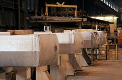 Aufgebockte Aluminiumblöcke in der Werkshalle des Aluminiumwerks bei Hamburg Finkenwerder / Altenwerder.