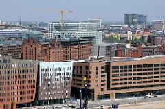 Architektur in der Hamburger Hafencity - Bürohäuser, Geschäftshäuser am Überseequartier - im Hintergrund Speicherhäuser der historischen Speicherstadt.