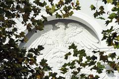 Stuckdekor an einer Hausfassade - Adler in Stein mit ausgebreiteten Schwingen.