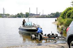 Slipanlage in Hamburg Rothenburgsort - ein Motorboot wird von seinem Trailer am Elbpark in die Elbe gelassen - im Hintergrund Industrieanlagen auf der Peute.