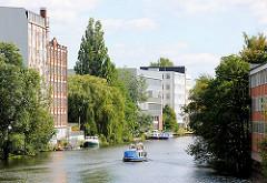 Historische und moderne Industriearchitektur am Mittelkanal in Hamburg Hamm - ein Motorboot fährt auf dem Kanal.