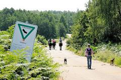Betonstrasse im Naturschutzgebiet Höltingbaum - Hunde sind an der Leine zu führen. Eine Spaziergängering hat ihre beiden Hunde an der Flexileine - im Hintergrund Pferd und ReiterIN.