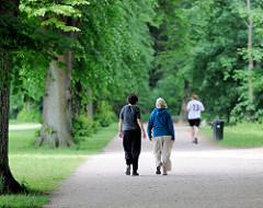 Spazierweg mit Spaziergängerinnen und Jogger unter hohen Bäumen im Volkspark Bezirk Hamburg Altona - Stadtteil Bahrenfeld.