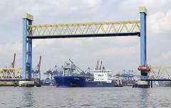 Ein Frachtschiff unterfährt die angehobene Kattwykbrücke; der Strassenverkehr ist in dieser Zeit unterbrochen.