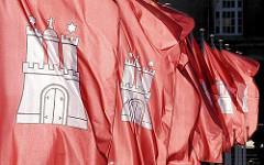 Flaggen der Hansestadt Hamburg am Rathausplatz - weisse Burg auf rotem Grund.