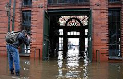Sturmflut in Hamburg - die Fischauktionshalle steh unter Wasser - ein Fotograf macht ein Foto.