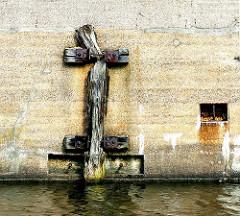 Alter Streichdalben an der Mauer eines Gebäudes im Kanal in Hamburg Billbrook - Bilder aus den Stadtteilen - Fotos aus Hamburger Bezirken.