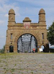 Portal der Harburger Elbbrücken mit Harburger Wappen - Kopfsteinpflaster - Denkmalschutz.