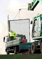 Ein abgetrenntes Teilstück des Eisenzollzauns wird auf einen Lastwagen verladen.