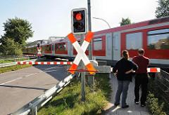 Bahnübergang Hamburg Süllfeld. Die BAhnschranken sind heruntergelassen - ein Zug der Hamburger S-Bahn fährt Richtung Wedel vorbei.