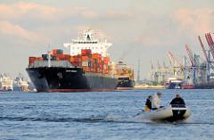 Das Containerschiff Santa Rebecca auf der Elbe - der Frachter hat eine Länge von 281 m und kann 4112 Container TEU transportieren; im Vordergrund ein Schlauchboot in Fahrt.