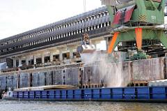Güterumschlag im Hamburger Hafen - Schüttgut wird mit einem Greifer aus einem Binnenschiff geladen.