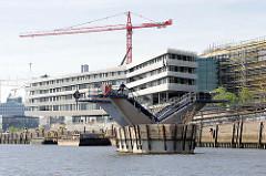 Baustelle der Hamburger HafencityUniversität  am Versmannkai im Hamburger Baakenhafen - der Bau einer Brücke über das Hafenbecken hat begonnen - einer der Brückenpfeiler ist fast fertig gestellt.