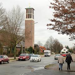 Kirchturm der St. Thomaskirche in Hamburg Hausbruch - Passanten, Spaziergänger auf dem Fussweg .