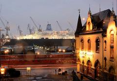Blick auf die Strasse St. Pauli Fischmarkt und zur Elbe, dem Hamburger Hafen - rechts ein Fischrestaurant mit beleuchteter Fassade - im Dock der Werft Blohm + Voss liegt eine Kreuzfahrtschiff.