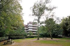 Hölderlinspark in Hamburg Winterhude - Ruhebänke in der Grünanlage - Balkons des Karl Schneider Blocks an der Stammannstrasse im Hintergrund
