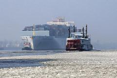 Das Frachtschiff COSCO GUANGZHOU läuft in den Hamburger Hafen ein - der Schlepper am Bug des Containerschiffs dirigiert den Riesen - ein Raddampfer der Hamburger Hafenrundfahrt fährt durch die Eisschollen der Elbe.