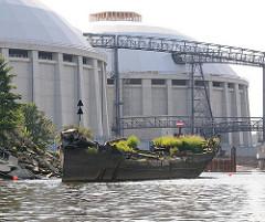 Baustelle Kohlekraftwerk Hamburg Moorburg am Ufer der Süderelbe - ein Schiffswrack mit Gras bewachsen liegt vor der ehm. Mündung der Alten Süderelbe.