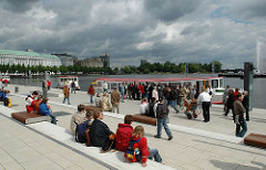 Alster Anleger Jungfernstieg - junge Leute sitzen auf den Treppen in der Sonne - Fahrgastschiff mit Fahrgästen am Schiffsanleger