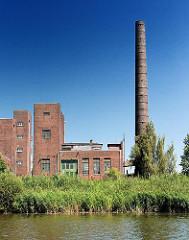 Gewerbliche Gebäude am Hoovekanal auf der Peute in Hamburg Veddel. Gebäude mit Klinkerfassade, hoher Schornstein; Gras am Ufer des Kanals in Hamburg Veddel.