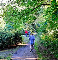 Jogger und Spaziergänger mit Hund im Sven-Simon-Park in Hambug Blankenese.
