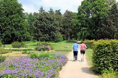 Spazierweg im Schulgarten vom Altonaer Volkspark - blühende Blumen - Jogger in der Sonne.