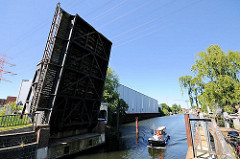 Geöffnete historische Holzhafenklappbrücke im Harburger Hafen. Ein Schiff verlässt den Holzhafen und fährt in den Lotsekanal ein.